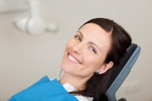 Woman sitting in dentist chair smiling after a painless root canal.