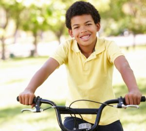 Young boy on a bike smiling wearing his traditional spaces to fix his smile.