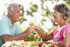 Elderly couple toast to good oral health and cosmetic dental services.
