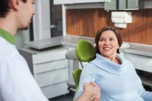 Woman in chair shaking hands with dentist talking about optional dental services.